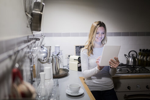 Smiling woman using tablet in kitchen - GIOF03679