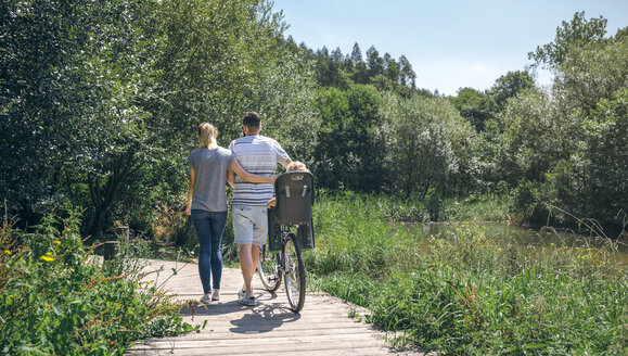 Family with bicycle walking on wooden walkway - DAPF00834