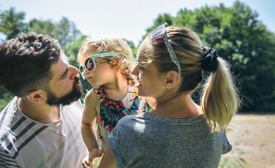 Little girl with sunglasses giving kisses to her parents - DAPF00840