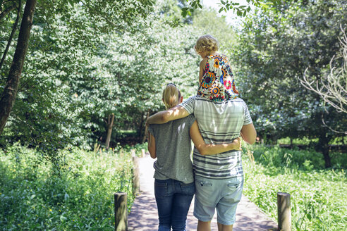 Family with little girl walking on a wooden walkway in the countryside - DAPF00843