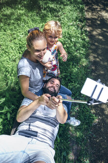 Happy man lying on a bench taking a selfie with his family - DAPF00849