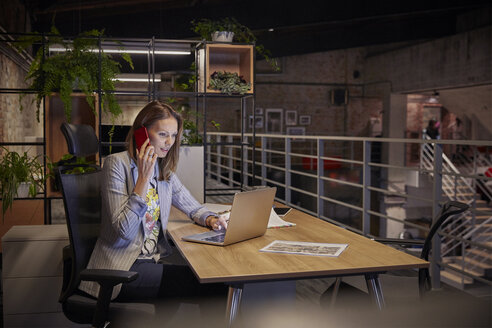 Businesswoman working in modern office, using laptop and phone - WESTF23778