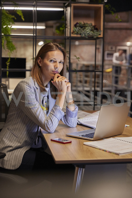 Businesswoman working in modern office, using laptop - WESTF23781