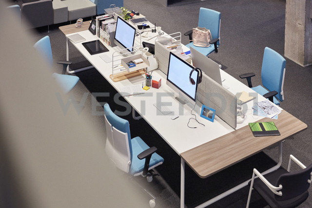 Desk in modern office with blank monitors - WESTF23787