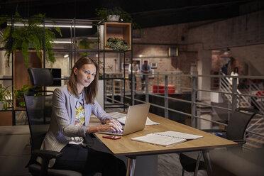 Businesswoman working in modern office, using laptop - WESTF23793