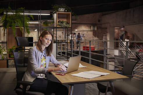 Businesswoman working in modern office, using laptop - WESTF23793