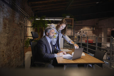Businessman and woman sitting in modern office, looking at laptop - WESTF23796