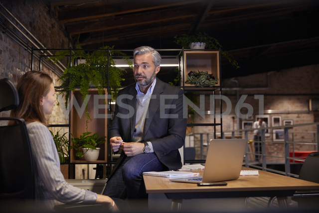 Businessman and woman sitting in modern office, talking to each oher - WESTF23799