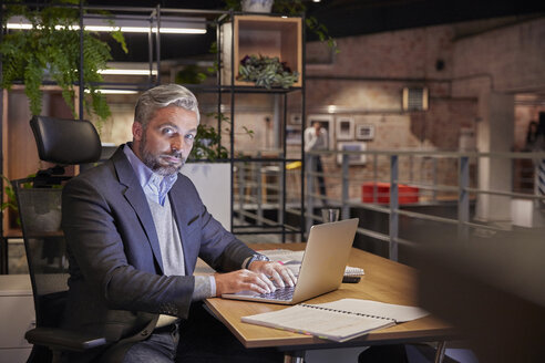 Mature businessman working in modern office, using laptop - WESTF23805
