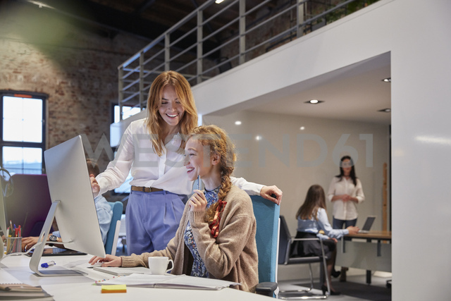 Young woman working in modern creative office, colleague giving advice - WESTF23811