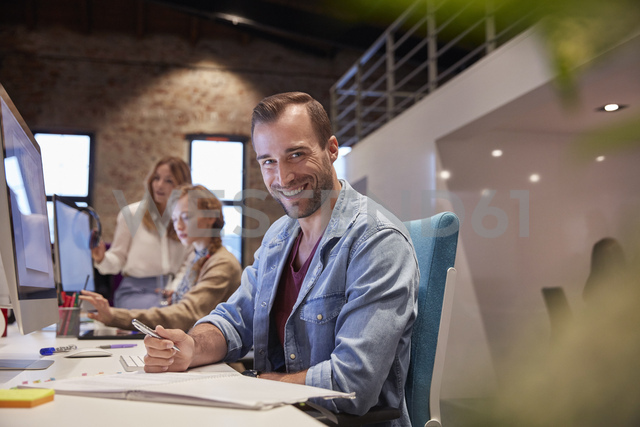 Man working at desk in office, smiling - WESTF23820