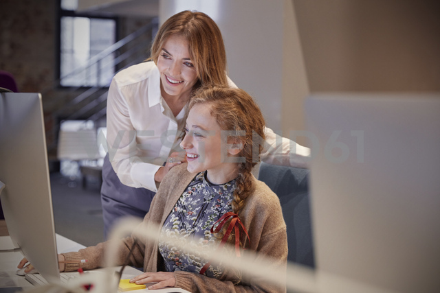 Colleague helping young woman at work - WESTF23823
