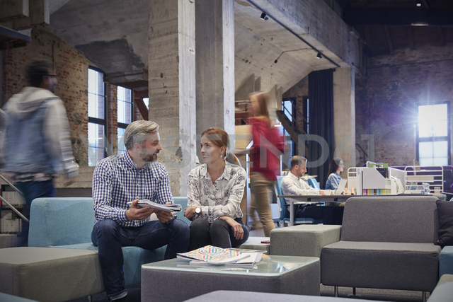 Business people having a informal meeting in communications pit - WESTF23862