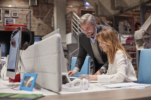 Businessman and woman working together in modern office - WESTF23874