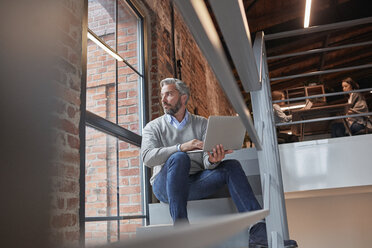 Businessman sitting on stairs of modern office, using laptop - WESTF23886