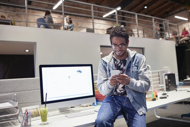 Young man working in creative start-up company, using smartphone - WESTF23892