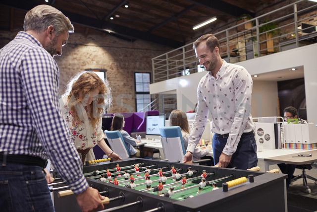 Business people in office taking a break, playing foosball - WESTF23901