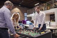 Business people in office taking a break, playing foosball - WESTF23901