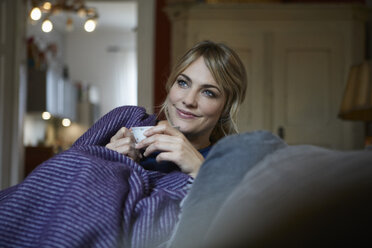 Portrait of smiling woman with cup of tea relaxing on couch at home - RBF06171