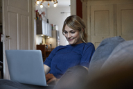 Portrait of smiling woman using laptop on couch at home - RBF06174
