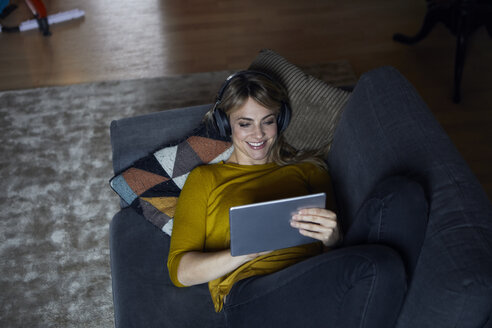 Portrait of smiling woman lying on couch using headphones and tablet - RBF06177
