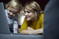 Portrait of mother and little daughter looking at laptop at home - RBF06180