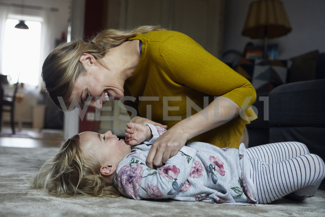 Mother and little daughter having fun together at home - RBF06186