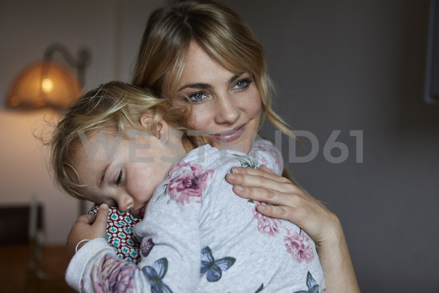 Portrait of happy mother holding sleeping little daughter on her arms - RBF06189
