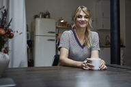 Portrait of smiling woman with cup of coffee sitting at table in the kitchen - RBF06192