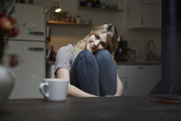 Portrait of smiling woman sitting in the kitchen - RBF06195