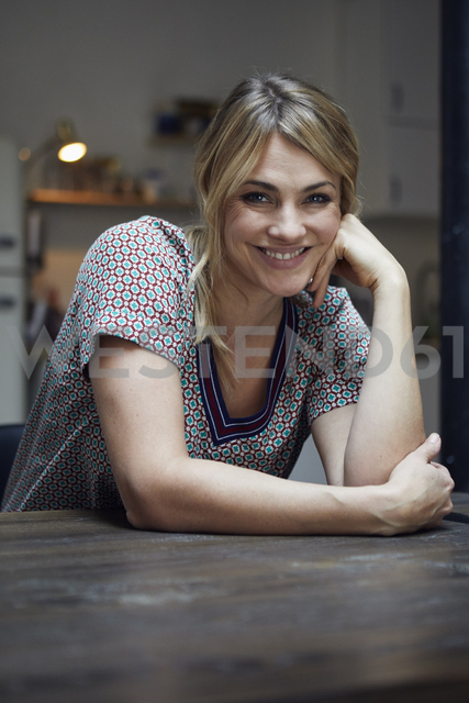 Portrait of laughing woman sitting at table in the kitchen - RBF06198 - Rainer Berg/Westend61