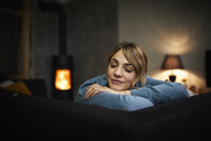 Portrait of woman relaxing on couch at home in the evening - RBF06201