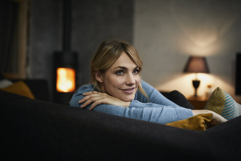 Portrait of smiling woman relaxing on couch at home in the evening - RBF06204