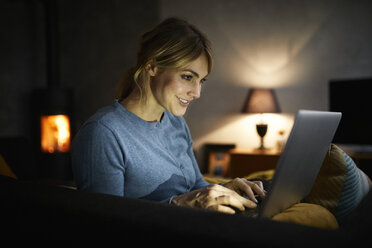 Smiling woman using laptop at home in the evening - RBF06207