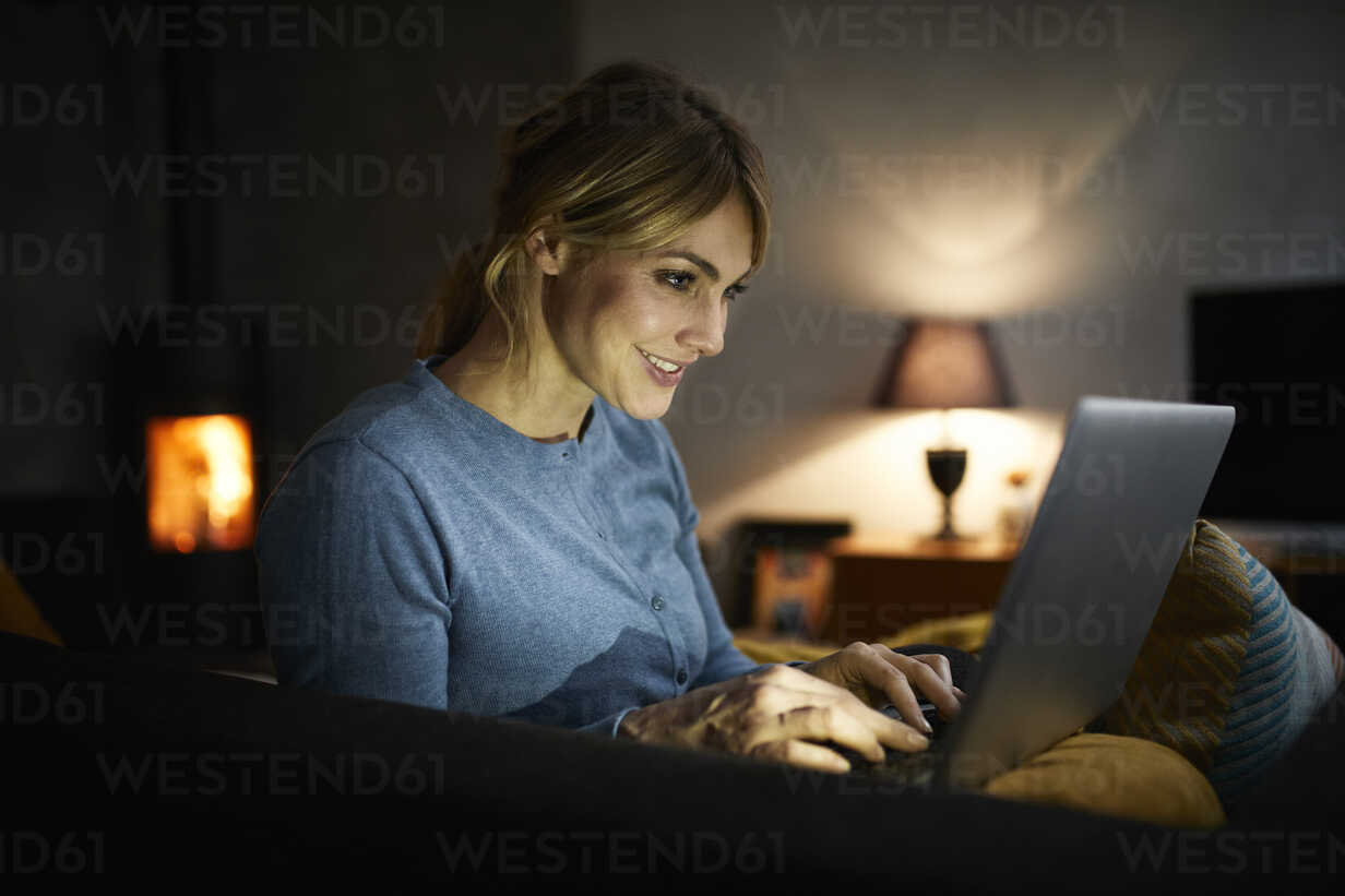Smiling woman using laptop at home in the evening - RBF06207 - Rainer Berg/Westend61