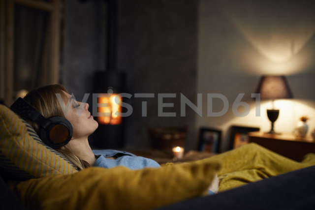 Smiling woman listening music with headphones on couch at home in the evening - RBF06210 - Rainer Berg/Westend61