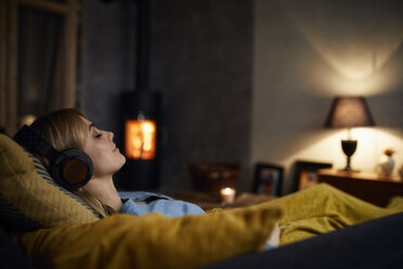 Smiling woman listening music with headphones on couch at home in the evening - RBF06210