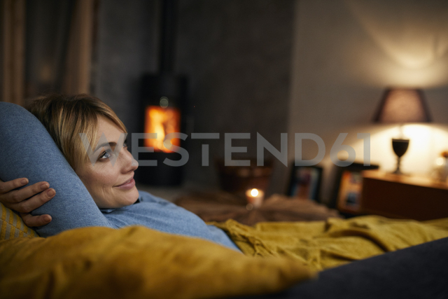 Smiling woman relaxing on couch at home in the evening - RBF06213 - Rainer Berg/Westend61