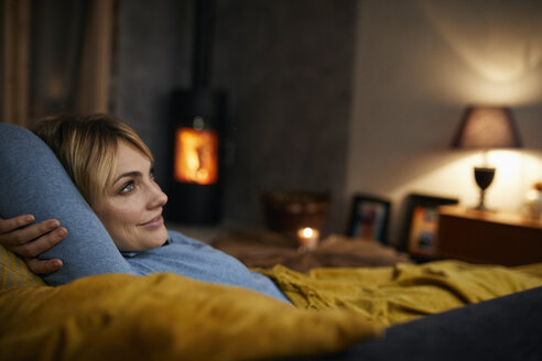 Smiling woman relaxing on couch at home in the evening - RBF06213