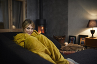 Portrait of smiling woman relaxing on couch at home in the evening - RBF06216