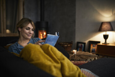 Portrait of smiling woman reading a book on couch at home in the evening - RBF06219