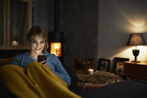 Portrait of smiling woman with smartphone relaxing on couch in the evening - RBF06222