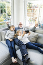 Two girls and grandfather on sofa taking a selfie - MOEF00520