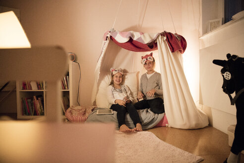 Portrait of two happy girls with tablet in children's room - MOEF00523