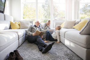Two girls and grandfather reading book in living room - MOEF00526
