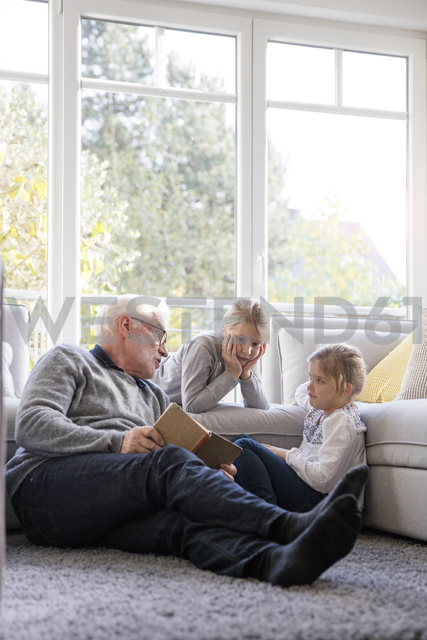 Two girls and grandfather reading book in living room - MOEF00529