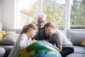Two girls and grandfather with globe in living room - MOEF00532