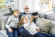 Two girls and grandfather on sofa taking a selfie - MOEF00538