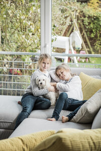 Portrait of two girls with dog on couch in living room - MOEF00544