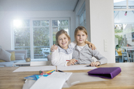 Portrait of two girls embracing doing homework at table together - MOEF00547